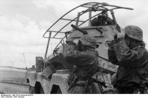 SS troops beside an SDKFZ 2328wheeler. This is a radio unit. The apparatus on top is an antenna not a roll bar.