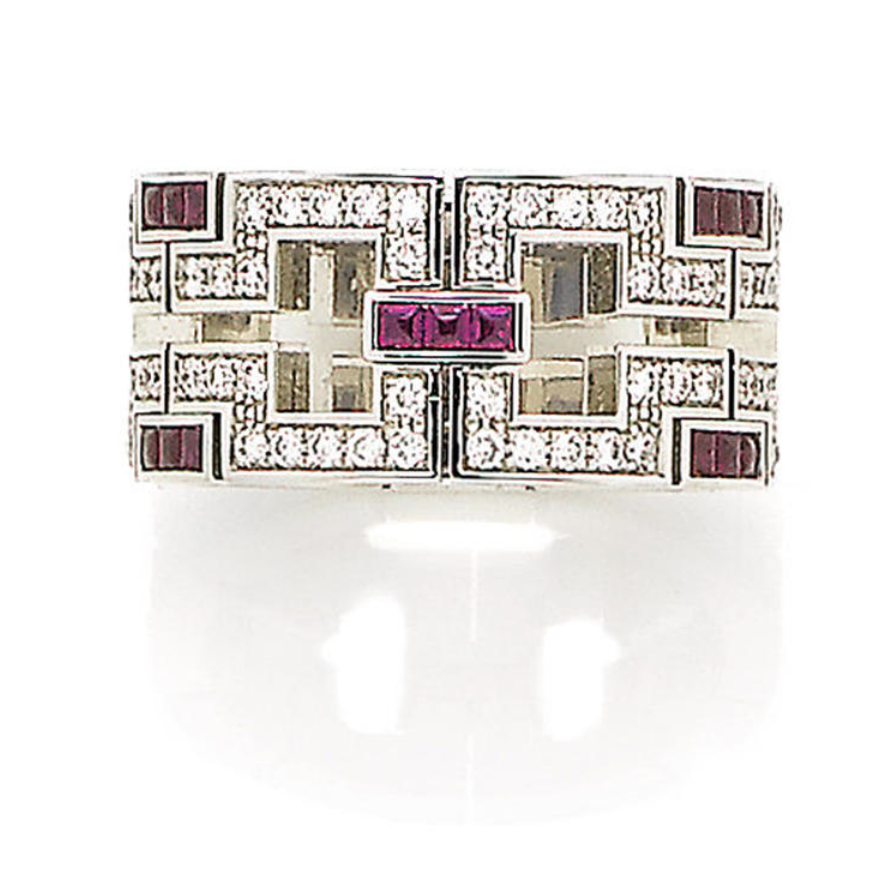 A ruby and diamond band ring, by Cartier  The wide band of pierced geometric design, set throughout with single-cut diamonds and calibré-cut rubies, diamonds approx. 1.10ct total, signed Cartier and numbered, French assay mark, ring size S, maker's case