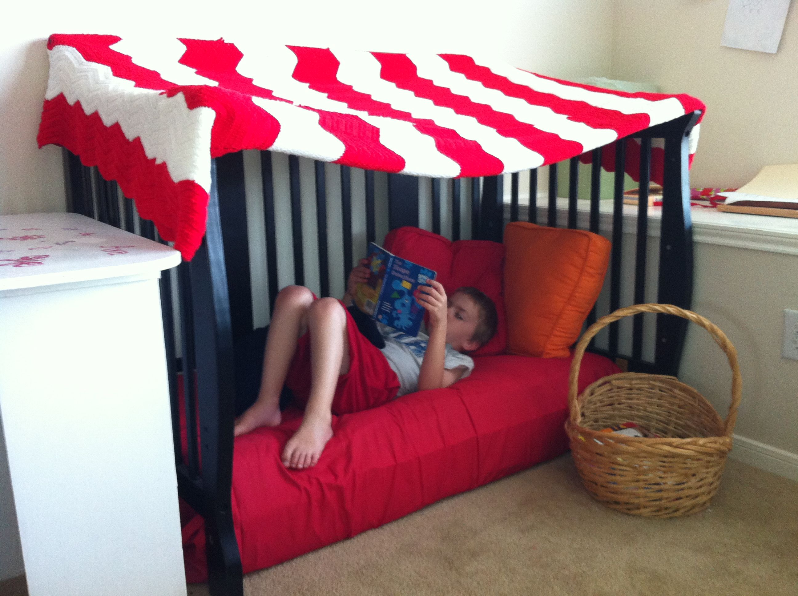 Kids reading nook / reading area. Repurposed baby bed with afghan