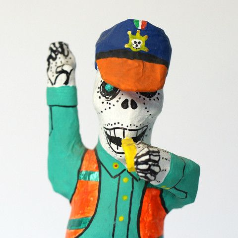 Paper mache Day of the Dead skeletons as police men. These long-legged fellows are primitive looking but were made by an expert paper mache artist from Mexico City. They stand on a wooden base.These guys have a whistle, a neon vest and their hands are up to stop traffic. If