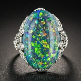 Few Australian 'Lighting Ridge' black opals come as fine as this this spectacular specimen presented in its original Art Deco splendor - circa 1930. The beautifully proportioned oval cabochon bursts with a multichromatic explosion of electric confetti colors against a deep black matrix background. The hand fabricated platinum mounting sparkles with three-quarter carats of diamonds. By Brock & Co., an early 20th century, high-end Los Angeles jeweler. Just shy of 1 inch long, ring size 7 1/2.