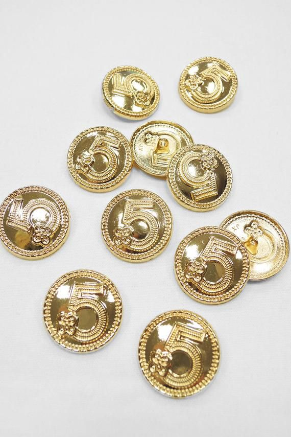Metal buttons in a Golden hue, decorated with a thin border and a black number 5 in the center. Buttons are not small, but light, have a beautiful Shine, like gold. Very convenient to use. We recommend using it for decorating suits and coats/ The price includes one button0929 - Button metal gold black number 5 edging  25mm0930- Button metal gold number 5 with edging 25mm0923- Button metal gold white enamel logo edging 17mm0924 Button metal 16 mm gold rope inside white enamel logo 16mm0925 Button