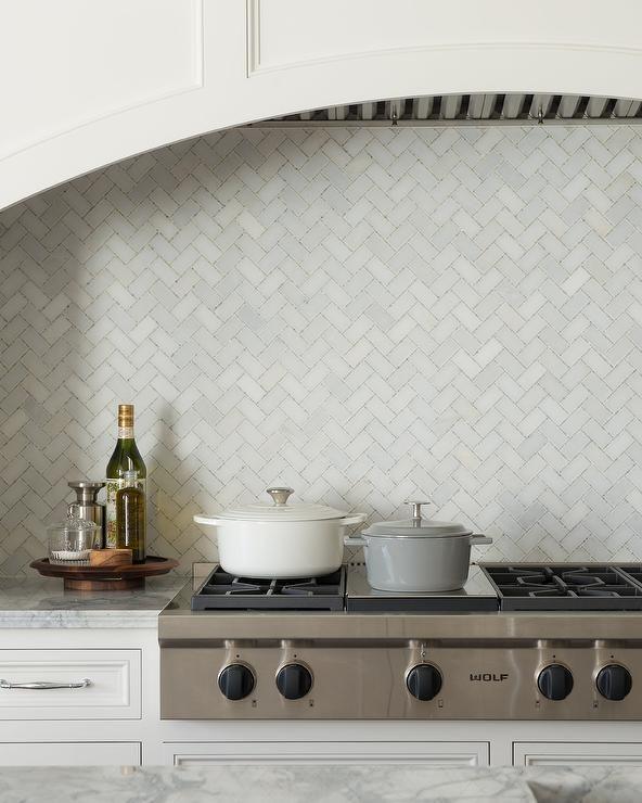 Morgan Harrison Home - Marble herringbone pattern tiles frame a
