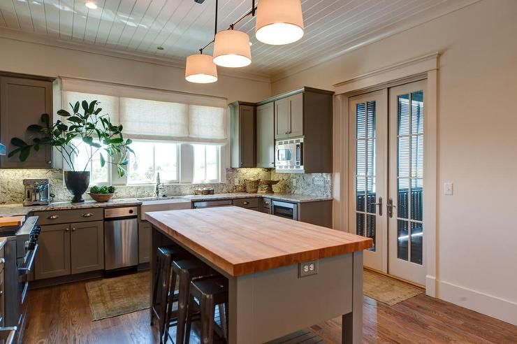 Cottage kitchen features a shiplap ceiling over grey ...