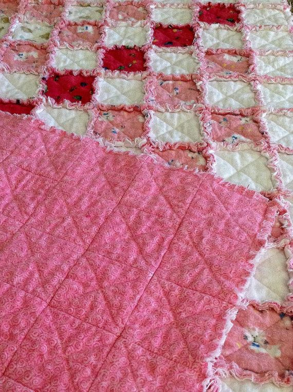 A handmade, warm and cuddly rag baby quilt measuring 36 1/2  X 45 1/2.  Made from cozy pink and white flannel for the top and back with