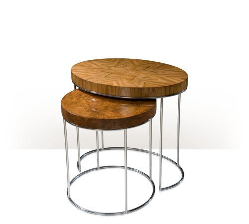A nest of two stainless steel and veneered tables, the larger oval blonde rosewood veneered table and the smaller circular walnut burl veneered table on tubular stainless steel legs.