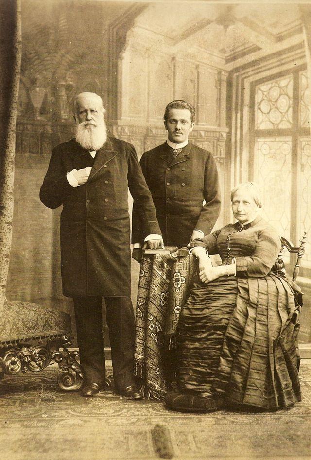 O imperador de barbas brancas com a mão direita escondida em seu casaco formal, fica ao lado da direita da Imperatriz assentado que usa um vestido hooped.  No fundo está um homem mais jovem no vestido formal. Pedro II, seu neto Pedro Augusto de Saxe-Coburgo-Gota e sua esposa Teresa Cristina de 1887.