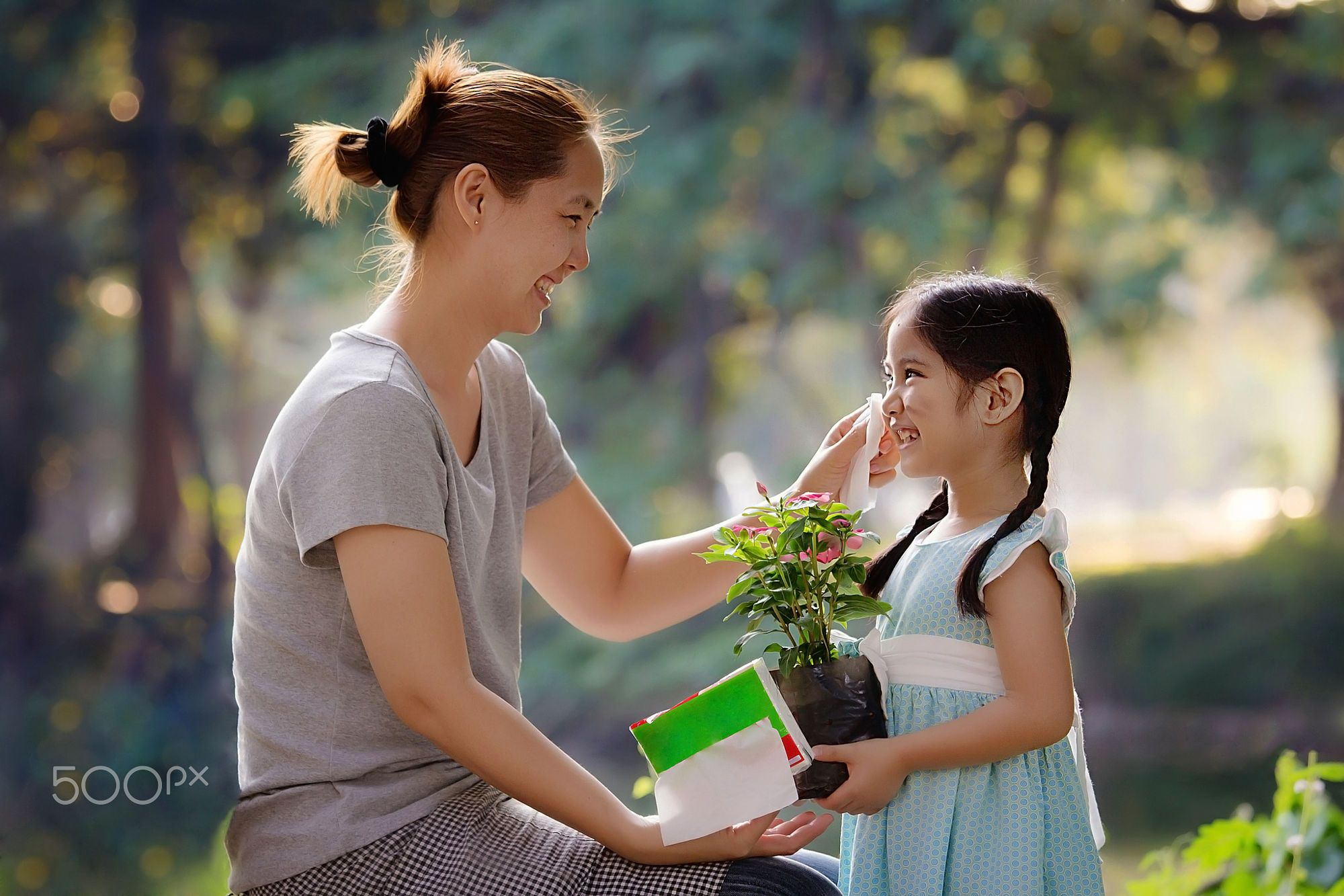 Asian mother cleaning her daughter's face, planting flower together