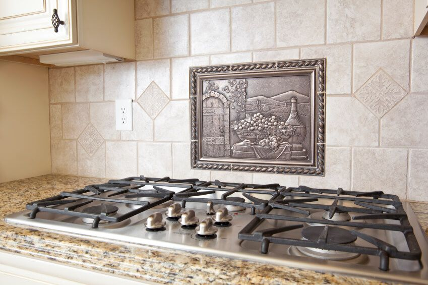 A Ceramic Tile Backsplash With A Metal Medallion Above The Range In A  Pastoral Scene.