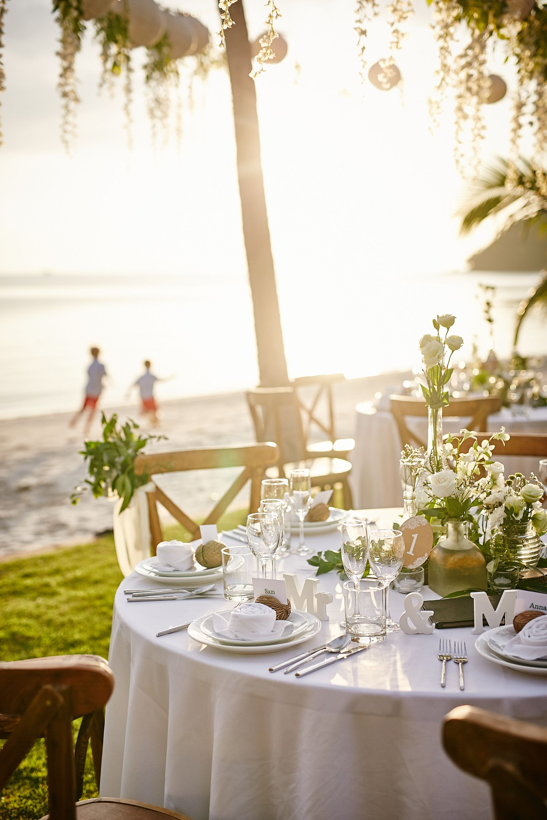 Beach Wedding Table Setting With White Flowers And Greenery