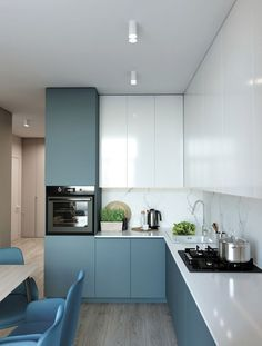 a minimalist blue and white kitchen with a white stone backsplash and white countertops is all chic - DigsDigs