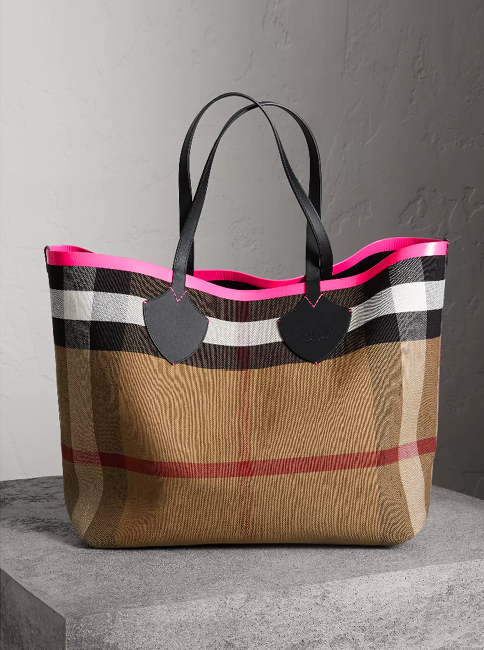 abe972eed132f1 A supersized reversible tote from Burberry in supple leather bonded to  Canvas check. Neon sealed seams add a clash of colour to the unisex bag.