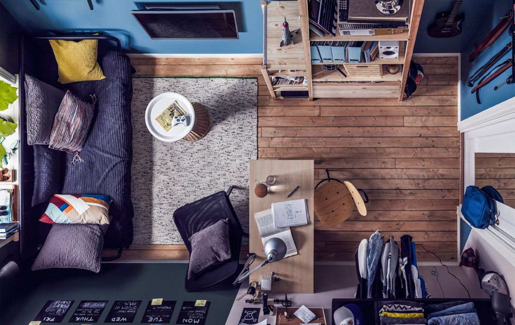 Oversigtsbillede over et lille teenageværelse med sovesofa, lektieområde og opbevaring