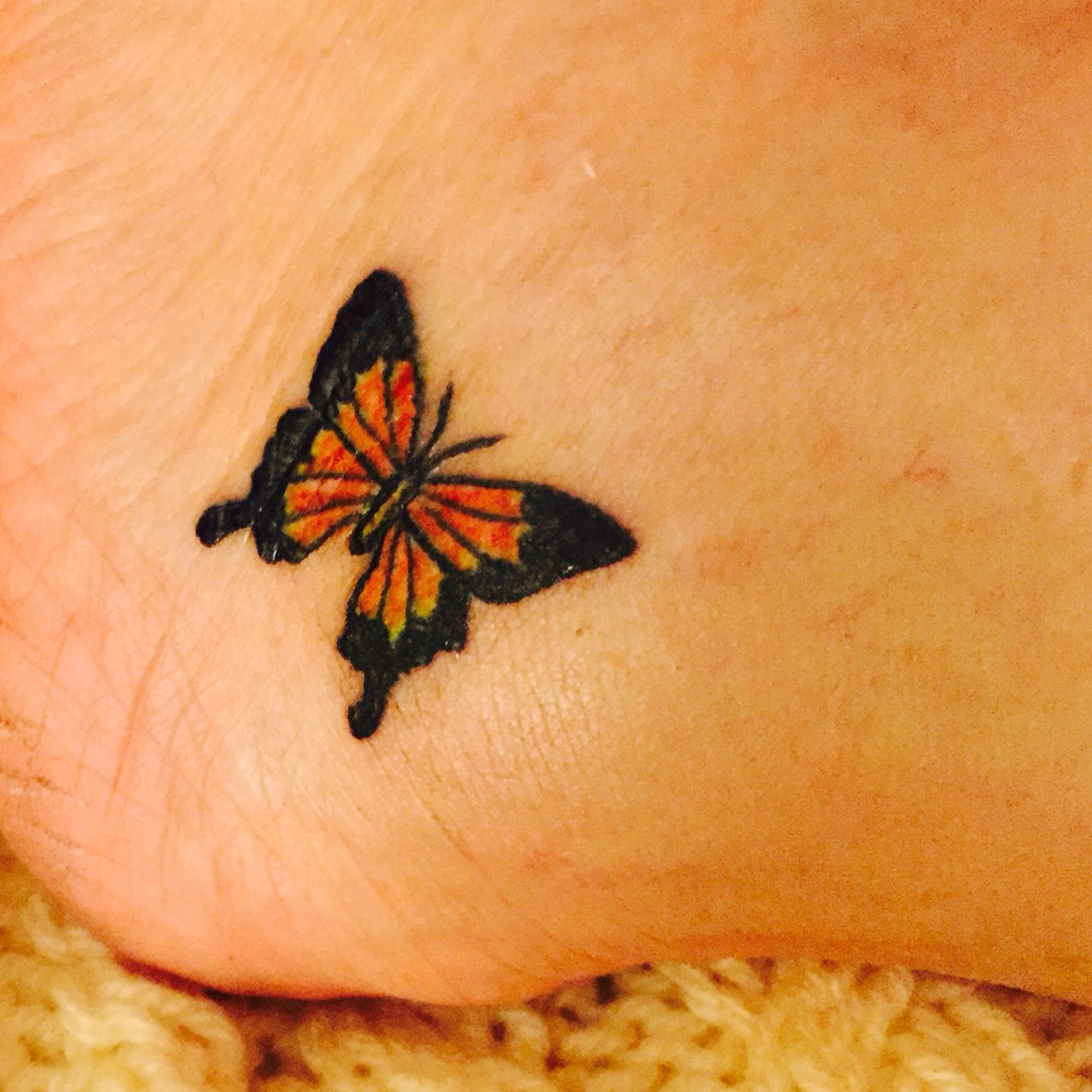 Small simple Monarch butterfly tattoo on lower ankle