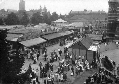 Kermis op het Vreeburg, op de achtergrond de Dom, Utrecht, Nederland 1914. Foto: Een overzicht van de kermis, met o.a. rechtsachter een deel van de achtbaan of rollercoaster.