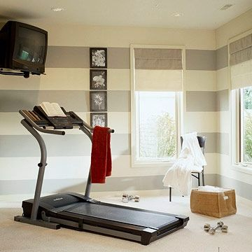 a workout room with a treadmill and a tv the light crisp