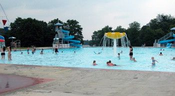 Families Enjoy The Blue Water And Sprayground Of The Pool