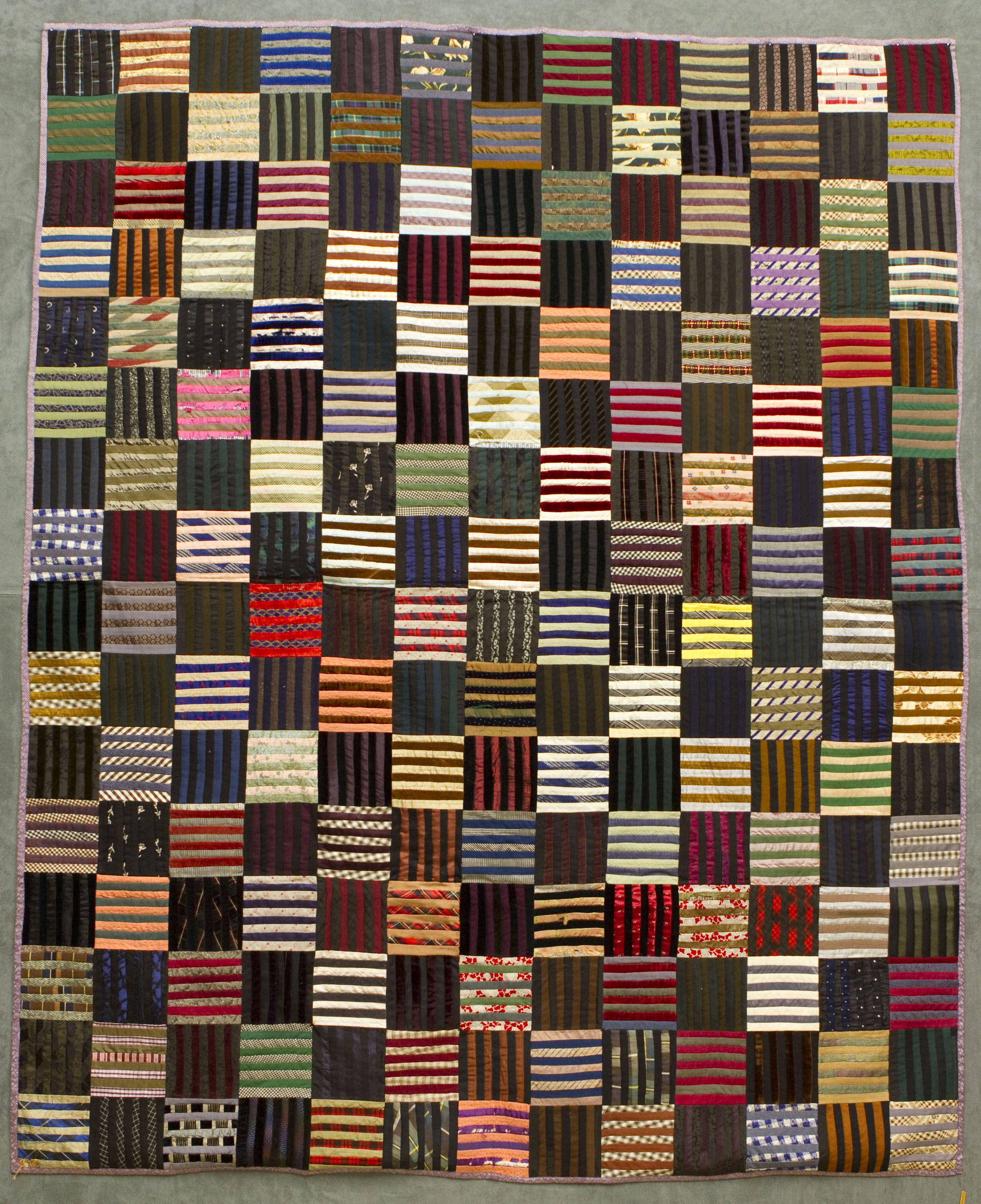The Roman Stripe Quilt was made in c.1900 by Mrs. Moss's grandmother, Mrs. Gregon McGowan in Blyth, Huron County, ON. It was brought to Edmonton, Alta. in 1923 when Mr. Moss got a botanist position at the U of A. The black fabric is from mourning clothes (popular during the Victorian era) re-cycled after use.