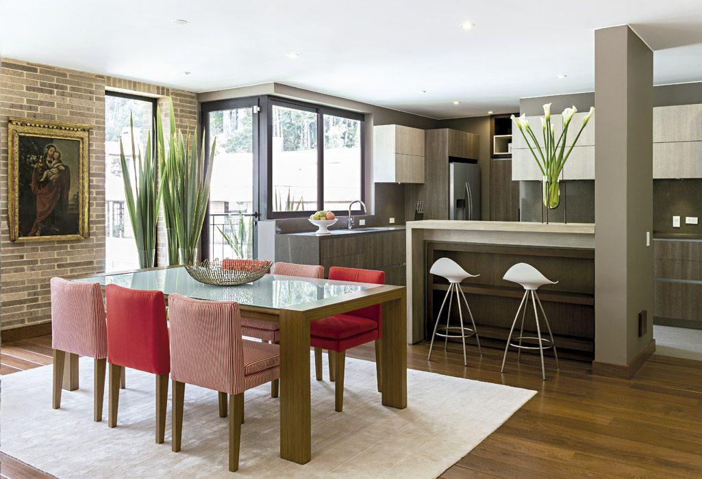 La moderna mesa del comedor, con vidrio blanco y patas de madera, y ...