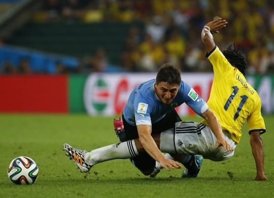 Uruguay's Diego Lugano (L) fights for the ball with Colombia's Juan Cuadrado during their 2014 World Cup round of 16 game at the Maracana stadium in Rio de Janeiro June 28, 2014. REUTERS/Kai Pfaffenbach