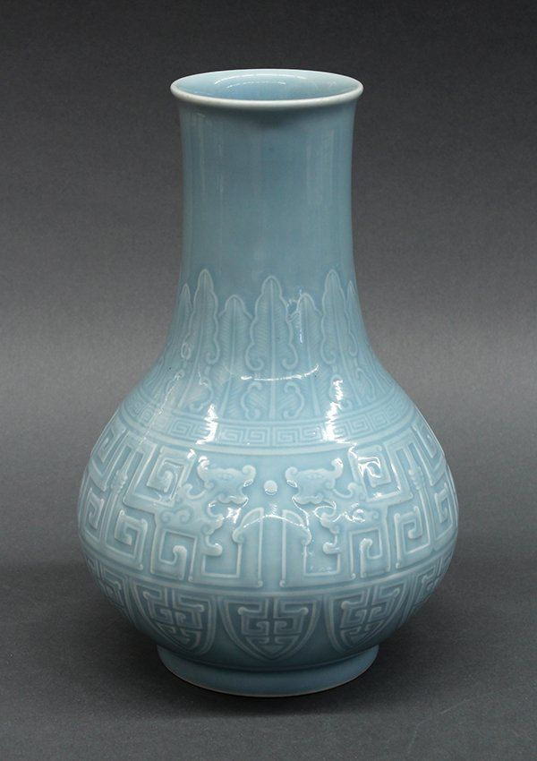 "Chinese blue monochrome porcelain vase, of hu-form molded with stiff leaf bands surrounding the neck, above gui-dragons and lappet bands, the base with an apocryphal underglaze blue Qianlong mark, 11.6""h"