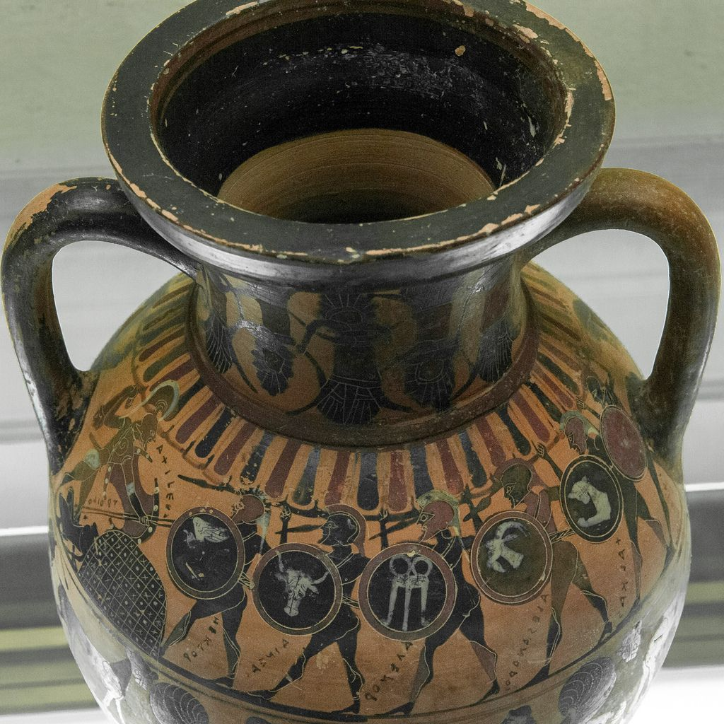"""This amphora reports one of the earliest known instances of the beheaded Troilos in Greek vase painting. The painter shows the beheaded corpse of Troilos lying to the left of an altar in shape of mound or """"omphalos"""". Based upon the prominence of the altar in the scene, it seems probable that the scene makes reference to the heinous murder occurring in the sacred sanctuary of Apollo Tymbraios. The young victim's name, ΤΡΟΙΛΟΣ, is inscribed in retrograde beside his body on both. The stance and…"""