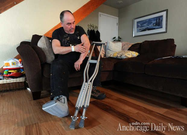 Iditarod musher Scott Janssen rubs a bruised arm while wearing a boot for his broken foot on Wednesday afternoon, March 5, 2014, at his south Anchorage home. Janssen, an Anchorage undertaker known as the Mushing Mortician, was airlifted off the trail to an Anchorage hospital early Wednesday morning for treatment for a concussion along with a broken bone.