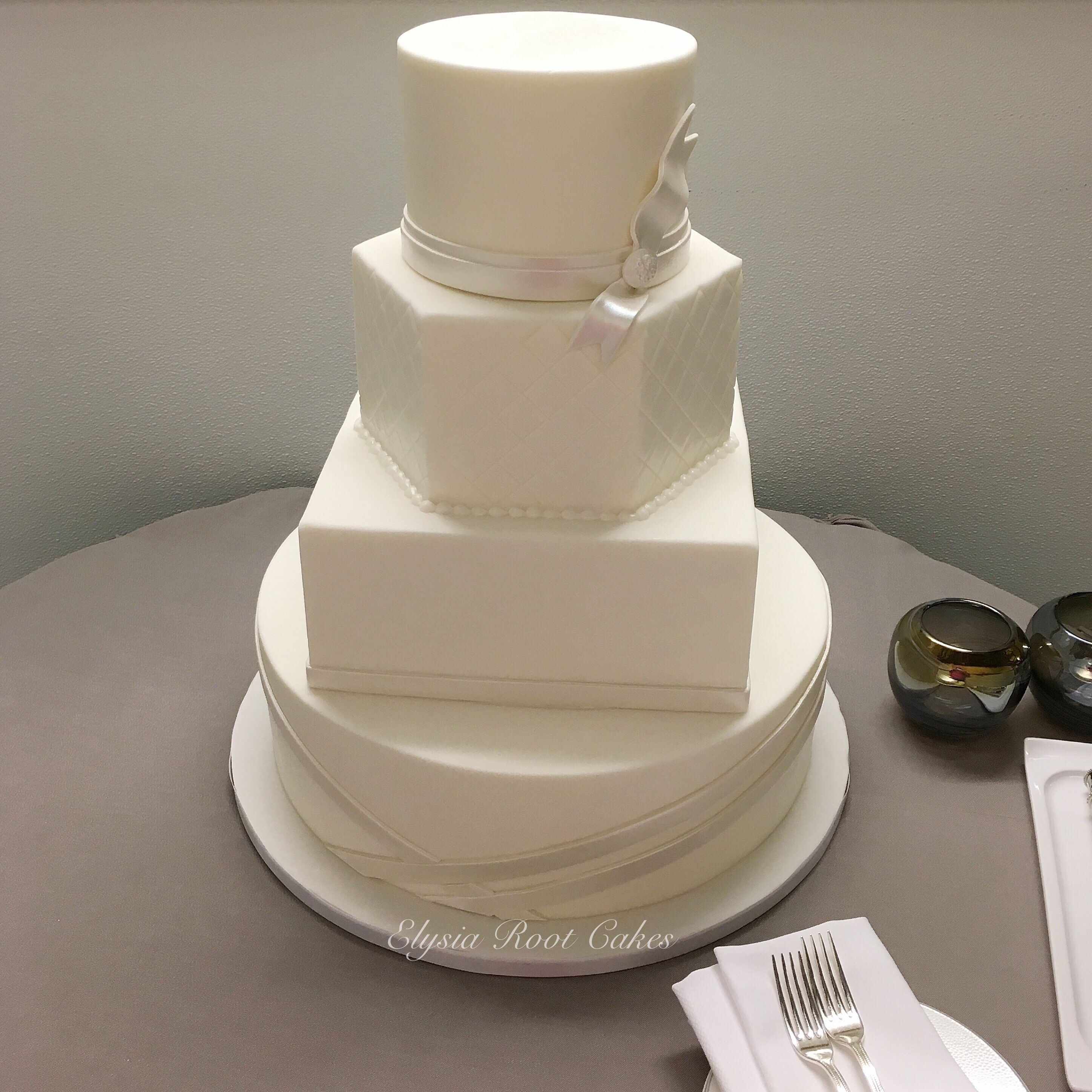 Weure loving all of the different shaped tiers for this wedding cake