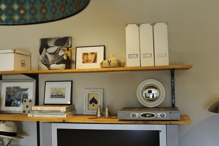 Pin for Later: Your Guide to Easy and Affordable Custom Shelves Stylish Storage Use the two shelves above the TV to hold more practical items like your cable box, files, and boxes and baskets for even more storage.