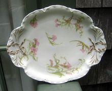 Antique Haviland Limoges Platter    Schleiger #472 On The Ranson Blank    Haviland Schleiger #472 is a pattern featuring pink carnations along with lilies of the valley and pink ribbons on the gently scalloped and embossed Ranson blank.    This pattern covers a major portion of this platter.    The back stamp is shown and dates it to the late 1800's.   $95.00