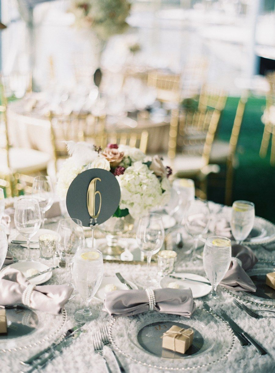 Beach themed wedding reception  Round table numbers complement the robust Deco font adding a subtle