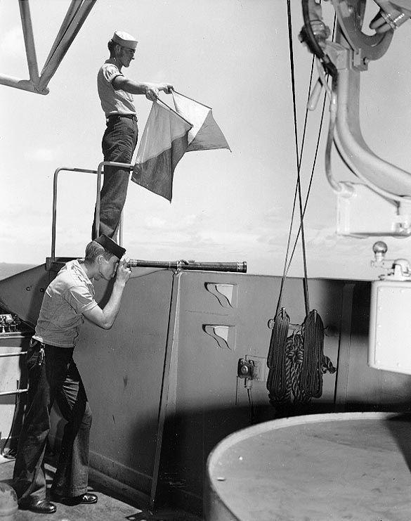 US Navy Signalman 2nd Class Kenneth Mitchell of battleship Colorado sending a message with semaphore flags, 29 Oct 1943; Signalman 3rd Class John Wilson on telescope. (US National Archives)