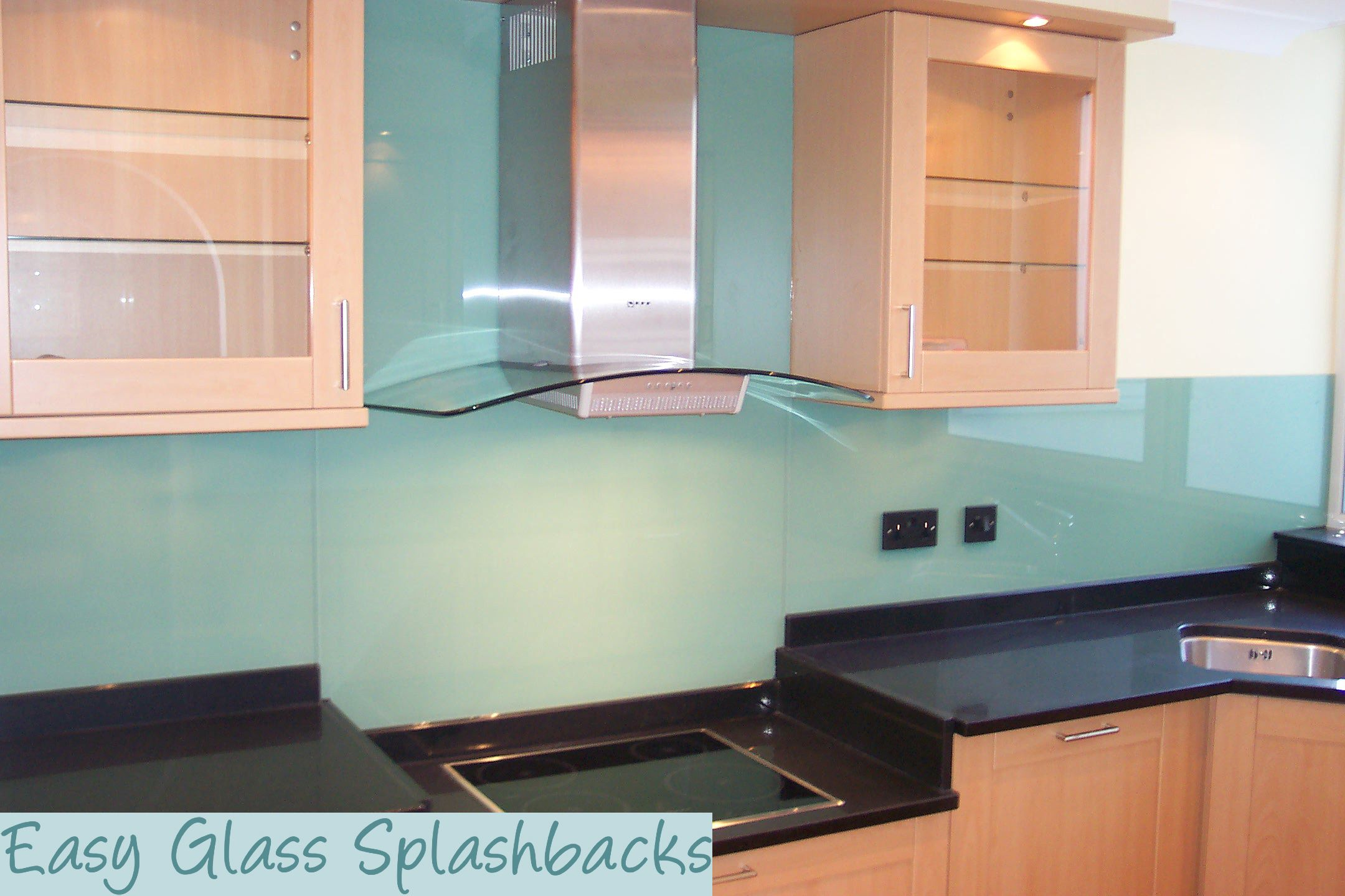 Mint Green coloured glass splashback in a Beech Kitchen with Black ...