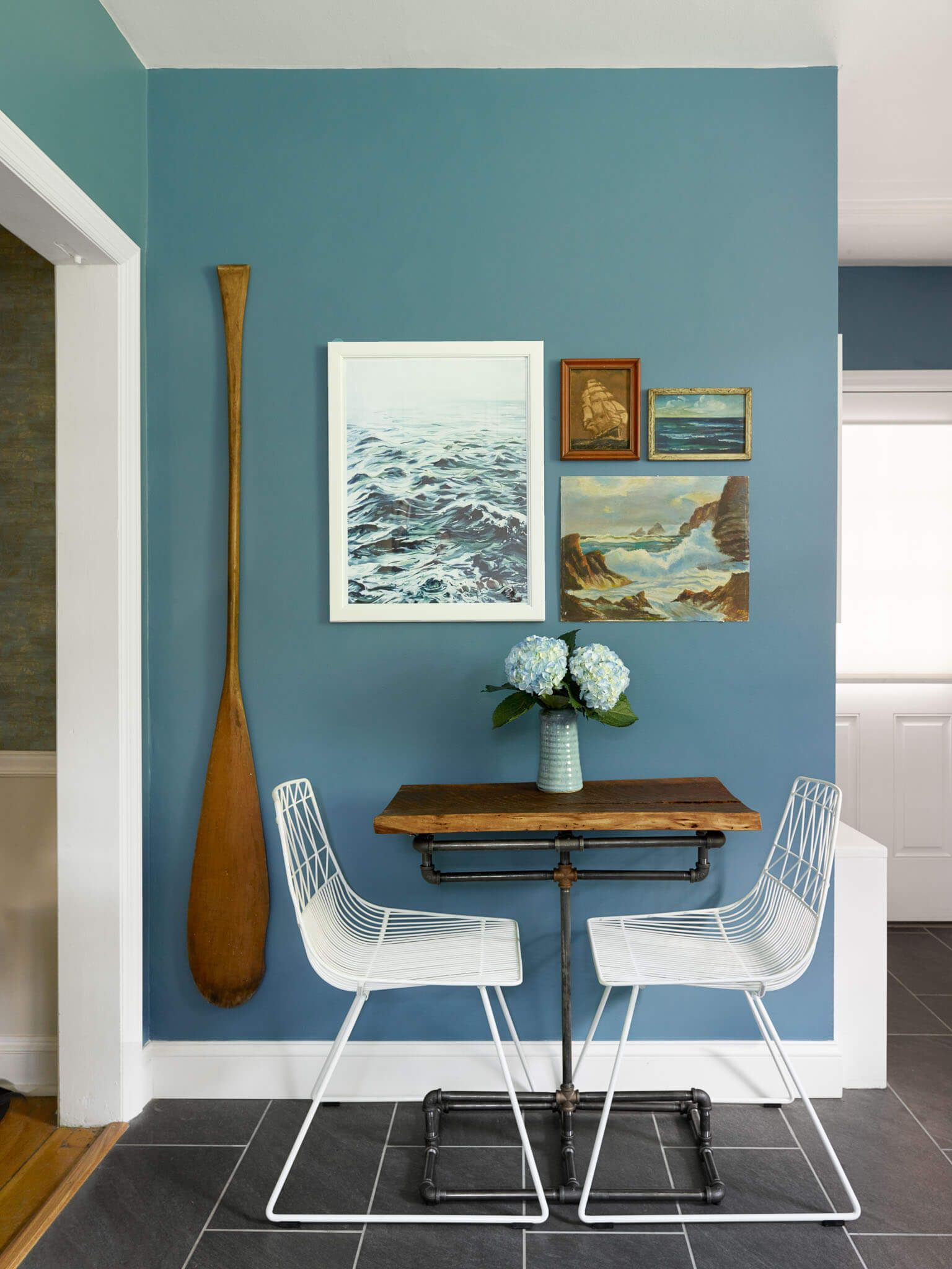 Gorgeous eat in kitchen area breakfast nook blue walls antique paddle as art vintage ocean and lake artwork modern coastal lake house vibe here