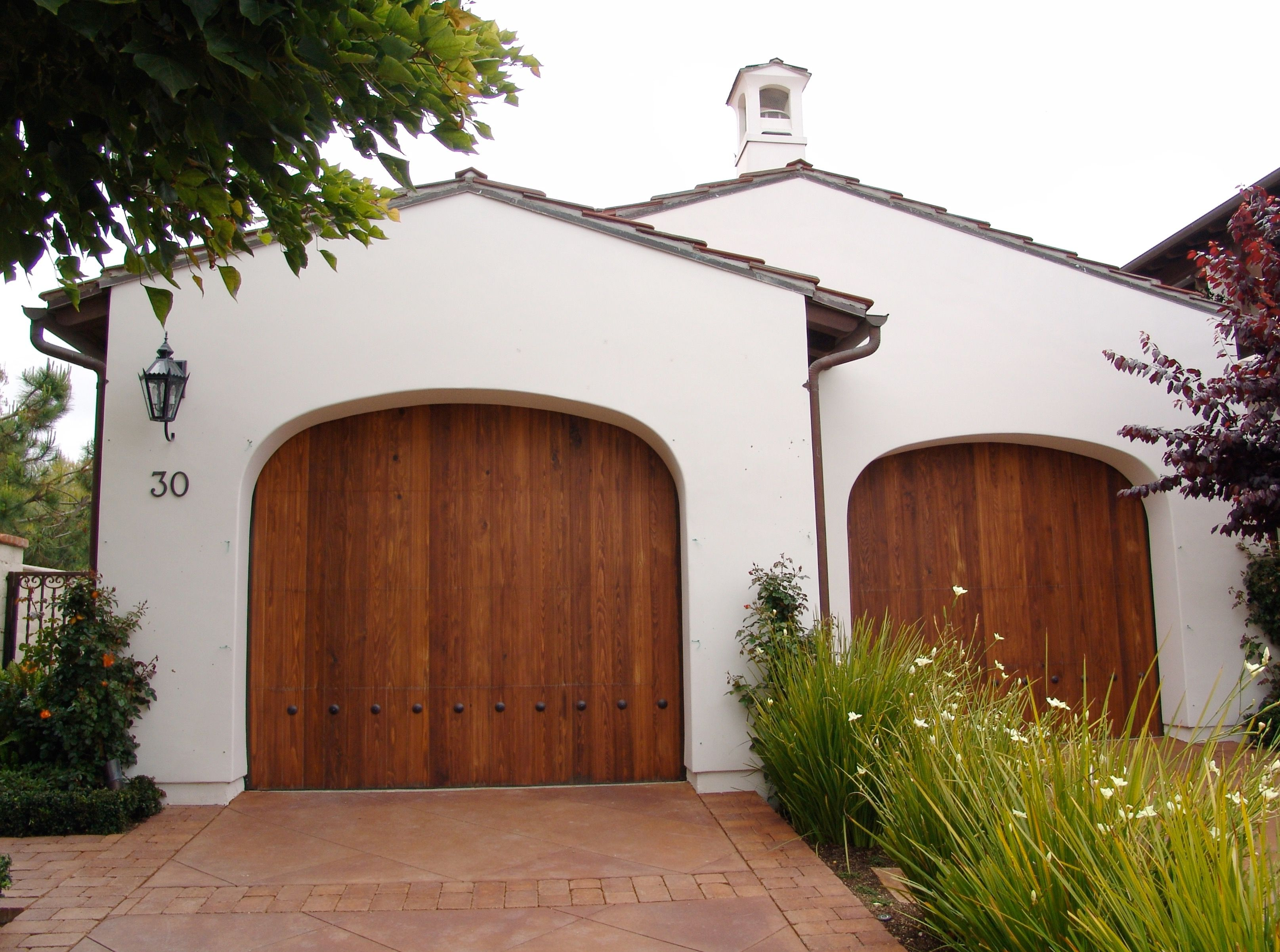 Spanish style garage doors made of african mahogany are clearly spanish style garage doors made of african mahogany are clearly the focal point of this front rubansaba