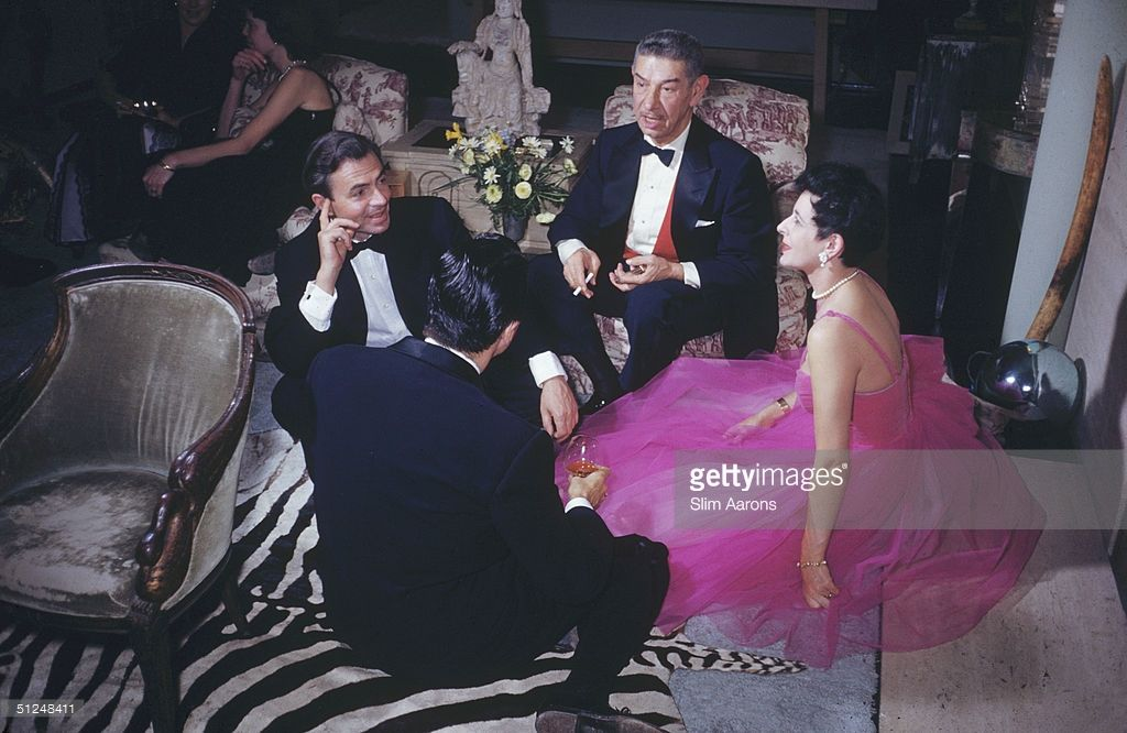 Stars chatting at a party at the Adrians' Beverly Hills home, 1954. From left to right, actor James Mason (1909 - 1984), restaurateur Mike Romanoff (1890 - 1972) and actress Pamela Mason (1918 - 1996).