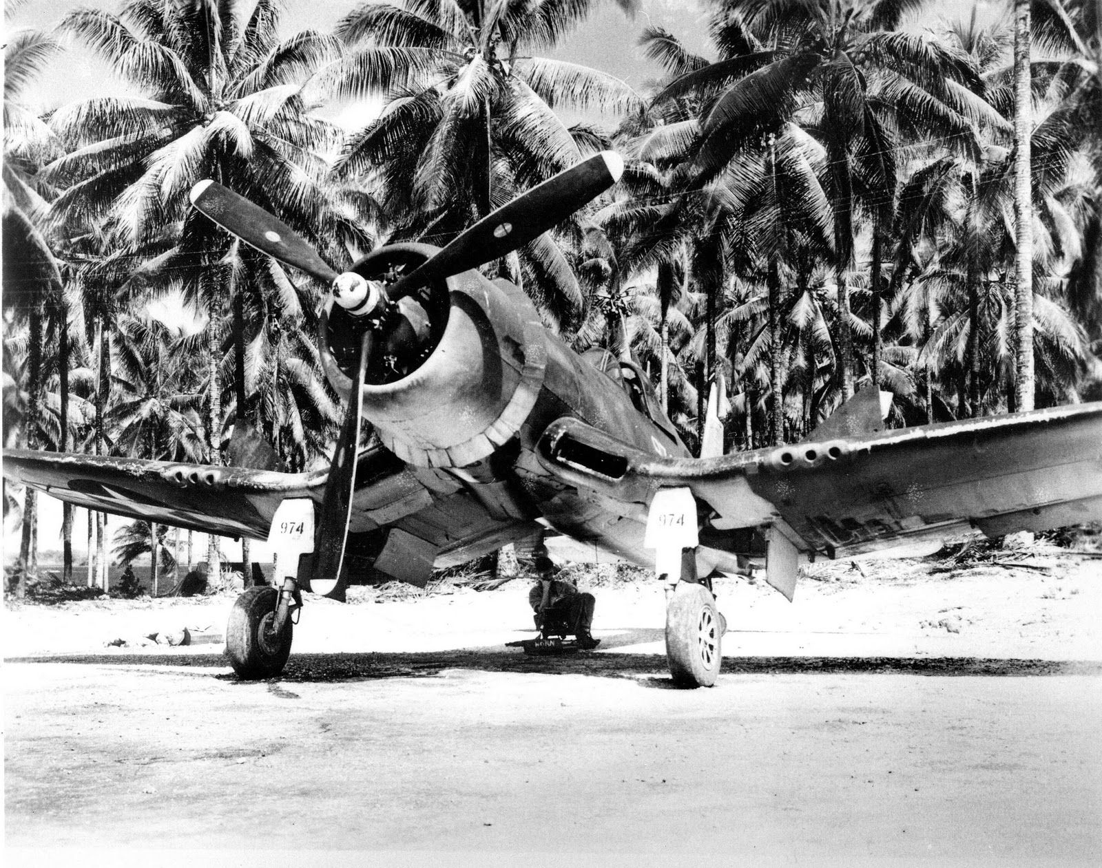 A crewman finds the only shade there is on the airstrip on Green Island (now…