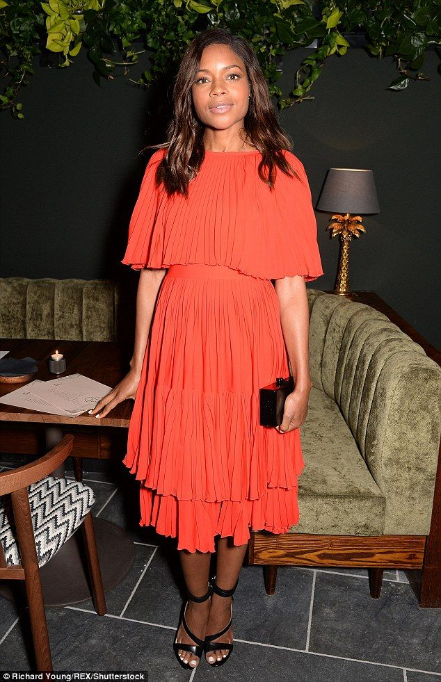 Bond beauty: Actress Naomie Harris stood out from the crowd in a vibrant orange ensemble w...