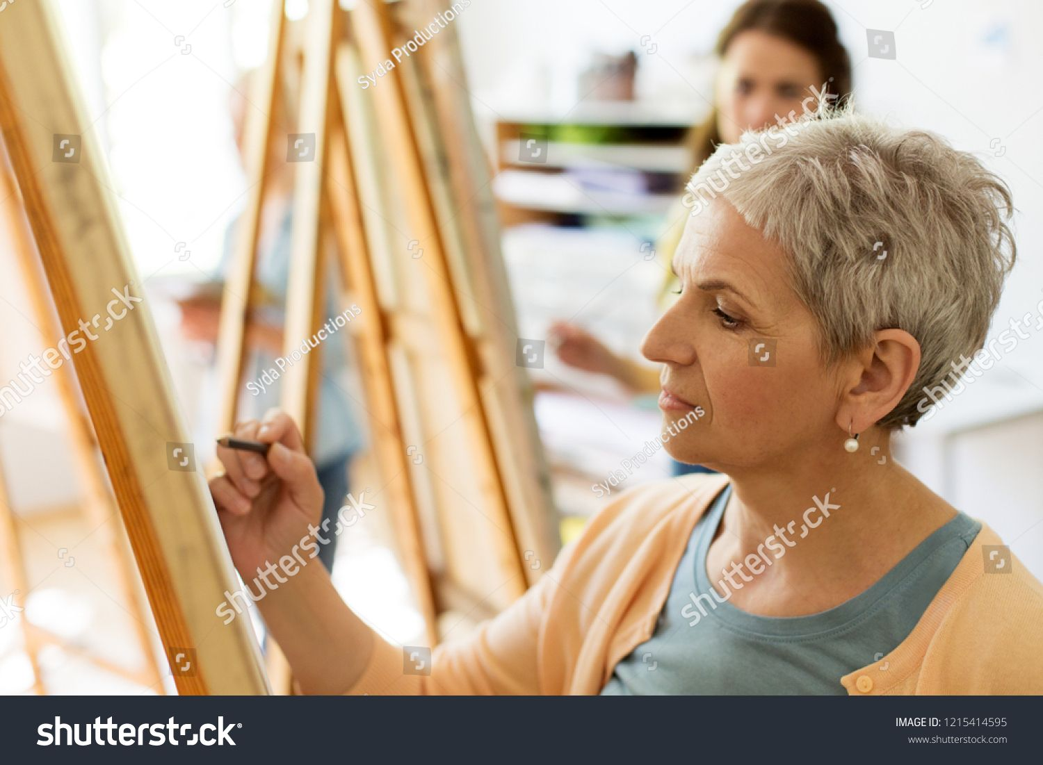 creativity, education and people concept - senior woman drawing on easel at art school studio #Ad , #Sponsored, #concept#senior#people#creativity