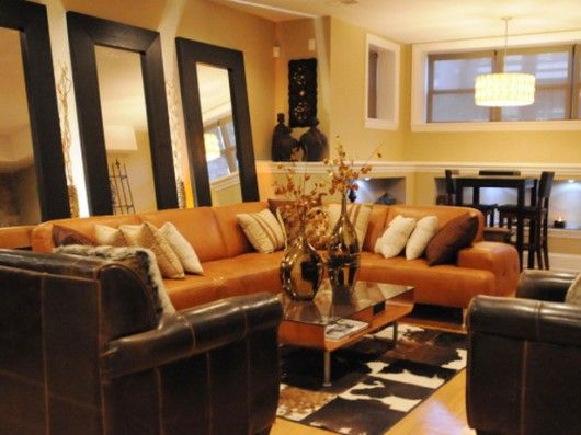 Delicieux A Comfortable, Lounge Living Room With A Warm, Inviting Color Palette.  Chocolate Brown Furniture And Accessories Complement The Large  Pumpkin Orange Sofa ...