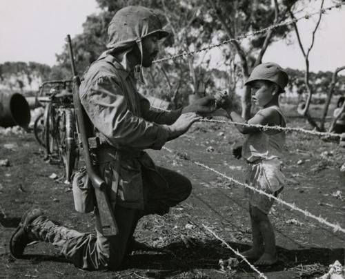 A US Marine stops beside the barbed wire fence of an internment camp on Tinian to give a native child some candy - 1944. (Photo by Corporal George Mattson)