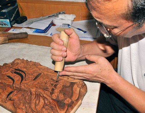 Работающий в традиционной манере мастер-резчик изготавливает деревянную печатную доску, оттиск с которой и будет няньхуа.: