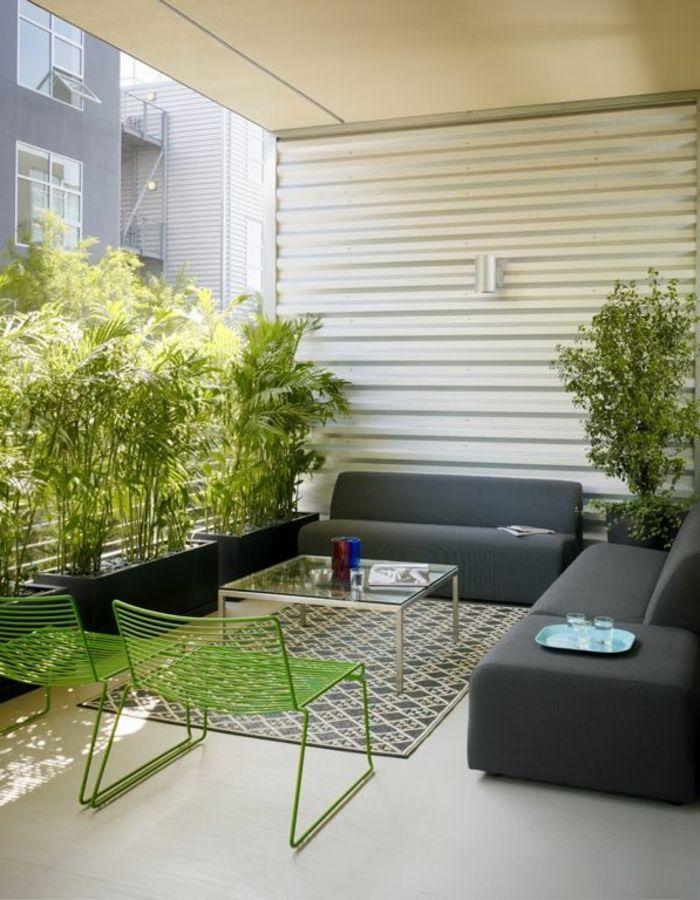 eine Terrasse mit Terrassenpflanzen in schwarzen Pflanzenkübel