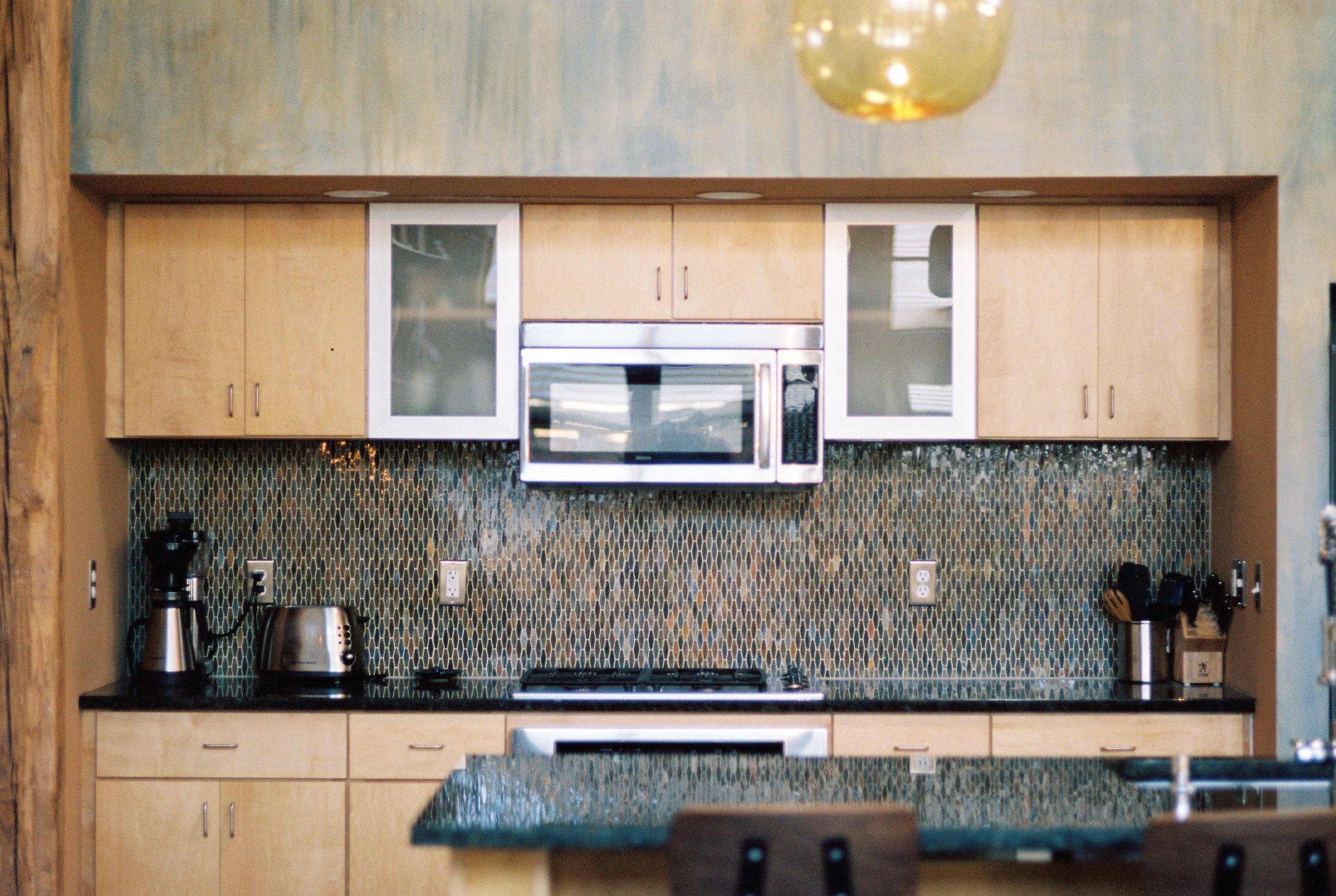 Simple modern kitchen with glass backsplash lava stone counters