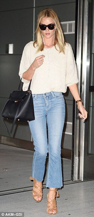 The 29-year-old model rocked a retro look in flared trousers as she touched down at JFK ai...