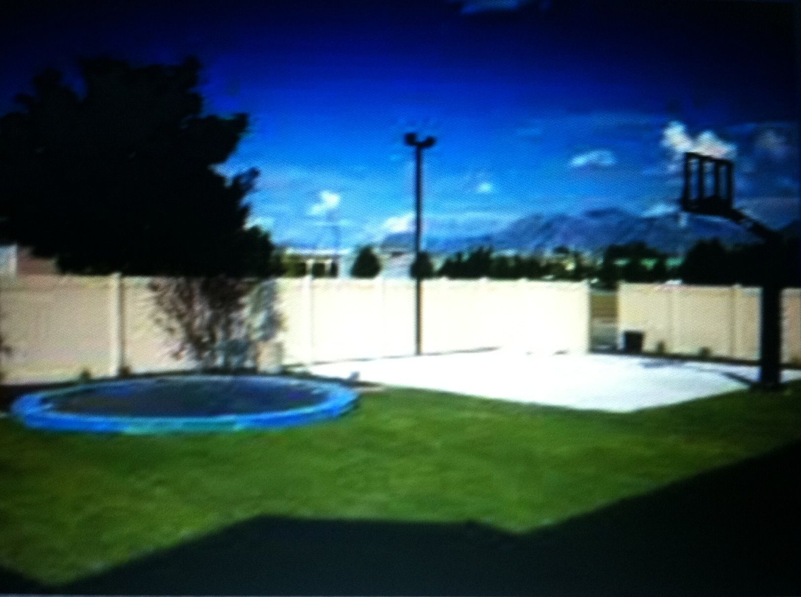 small basketball court in backyard in ground trampoline is nice