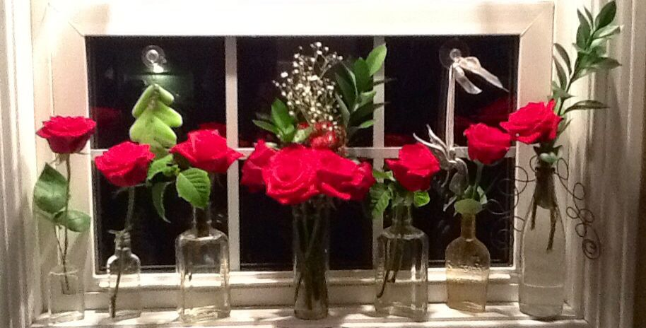 From a dozen roses in a large vase, to a single rose in an assortment of old bottles, and different small vases.