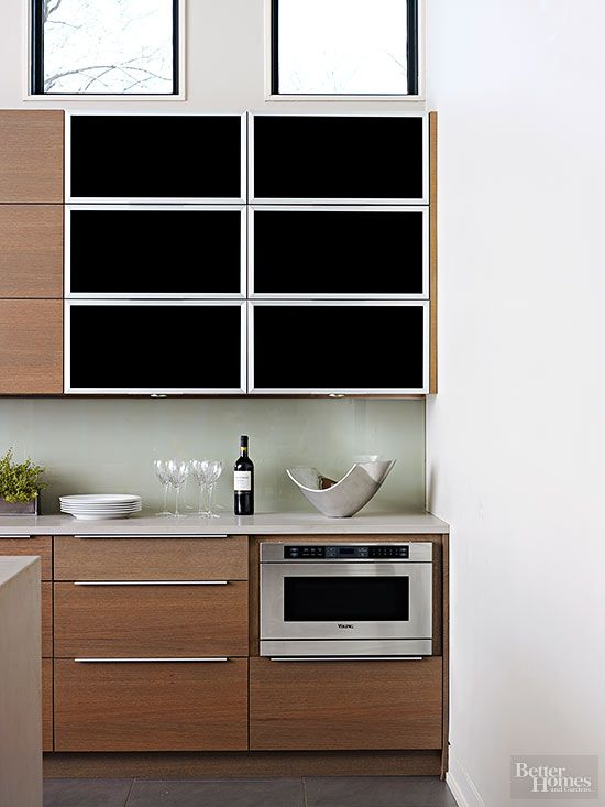No+cabinet+door+slamming+here.+Flip-up+cabinet+doors+with+pneumatic+hinges+ensure+smooth,+quiet+operation.+The+black+glass+doors+contrast+with+wood+cabinets+while+hiding+contents+from+view.
