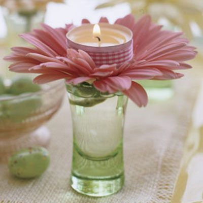 All you need are candles, ribbon, gerbera daisies, cordial glasses, and double-stick tape. Affix a length of ribbon around the metal rim of the votive. Snip off almost the entire stem of the flower, splay out the petals, and insert into the glass.