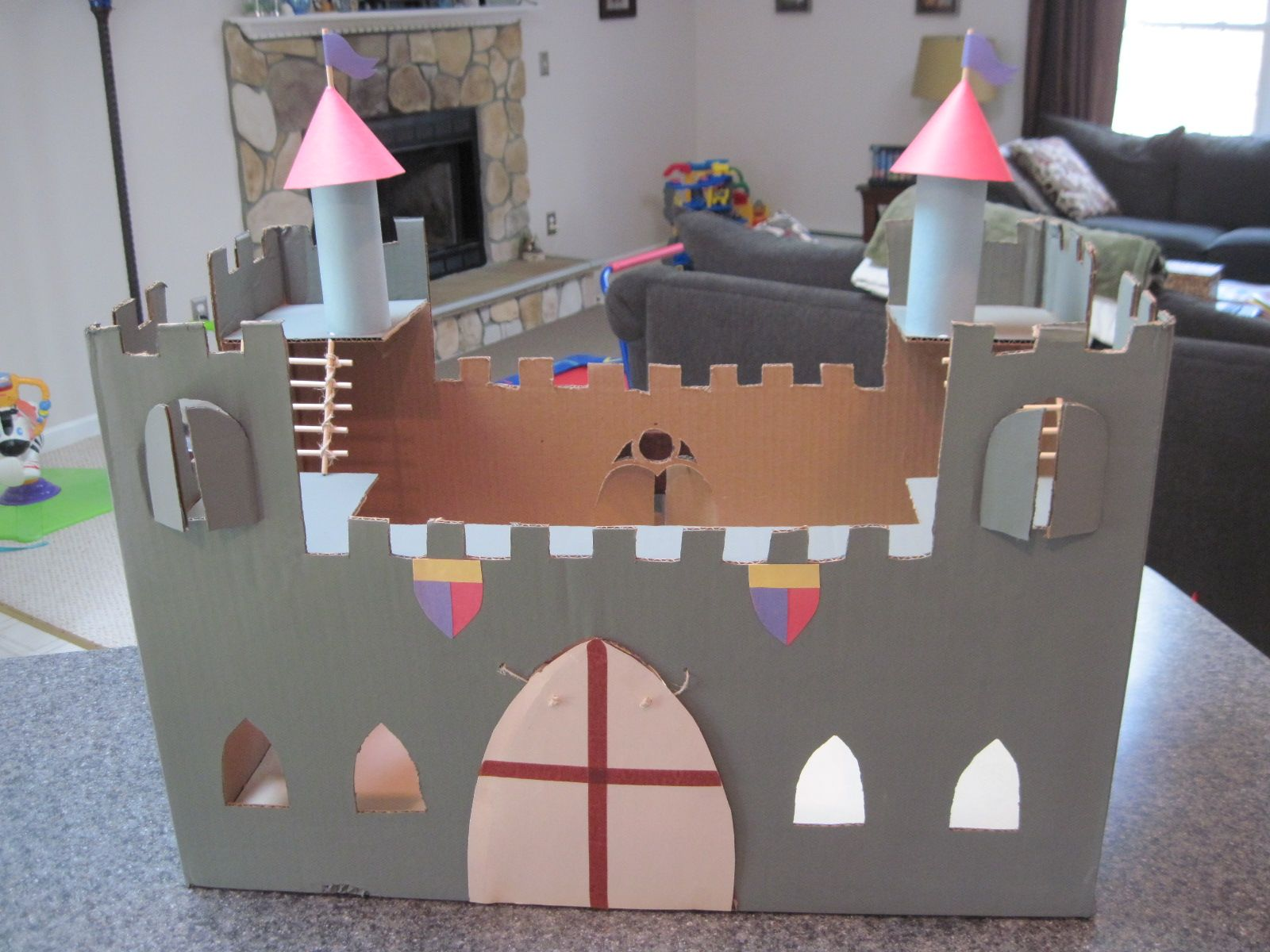 Cardboard box castle.  Twine for ladders & working drawbridge.  There's 2 windows each flanking the big window on rear wall.